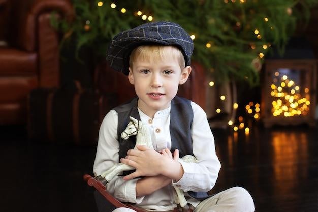 Kleine jongen knuffels beeldje van hobbelpaard op kerstmis