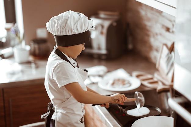 Kleine jongen kookt pannenkoeken in de moderne keuken