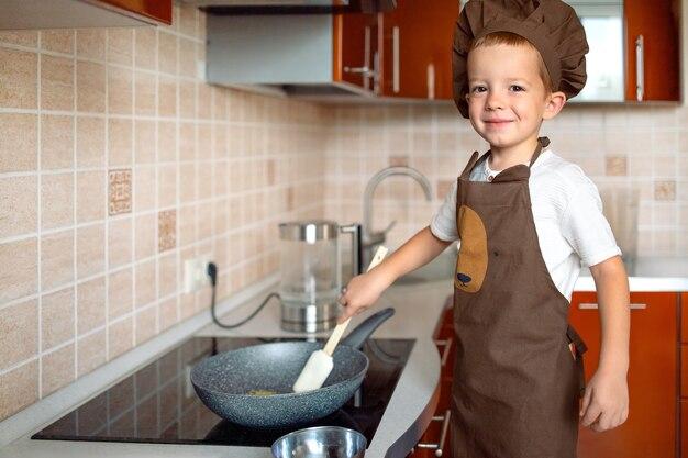 Kleine jongen kookt voedsel thuis in de keuken kijkend naar de camera.