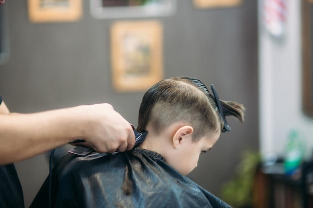 Kleine jongen krijgt kapsel door kapper zittend in de stoel bij barbershop.