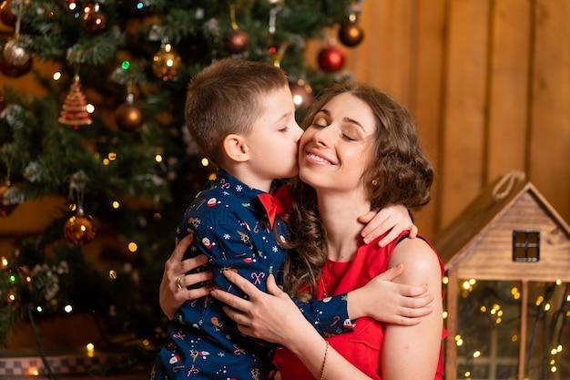 Kleine jongen kust moeder op de achtergrond van de kerstboom. gezinsvakantie, kerstverhaal