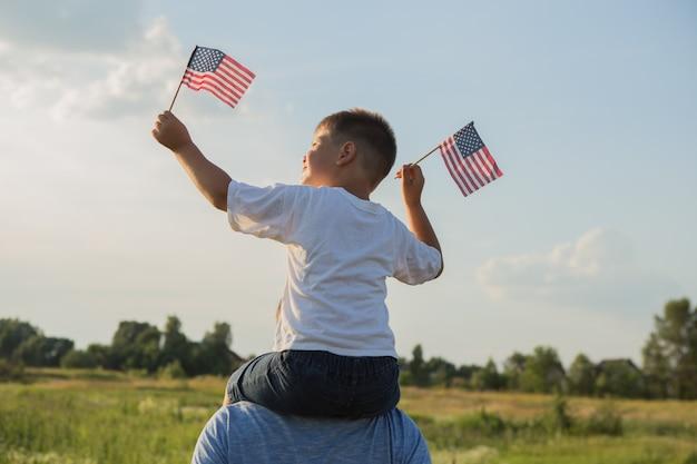 Kleine jongen laat de amerikaanse vlag in zijn handen vliegen op de wind op het groene veld