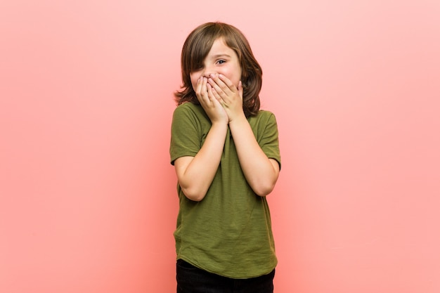 Kleine jongen lachen om iets, die mond bedekt met handen.