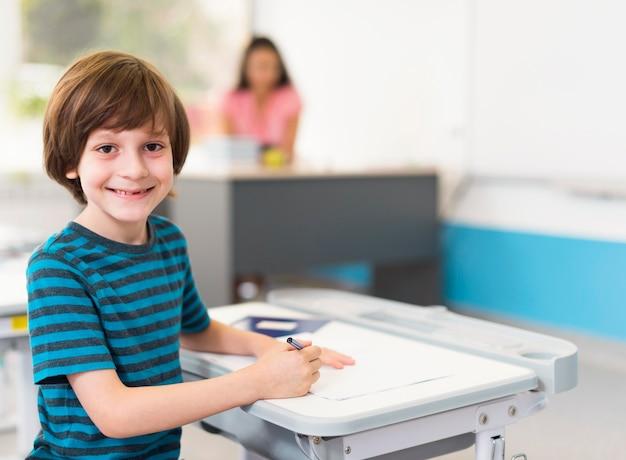 Kleine jongen lachend zittend aan zijn bureau