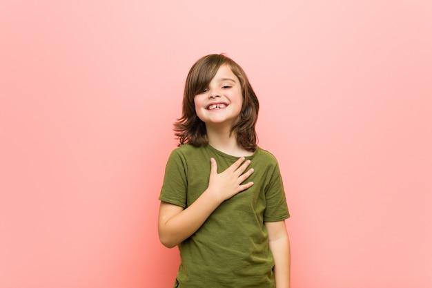 Kleine jongen lacht hardop terwijl hij de hand op de borst houdt.