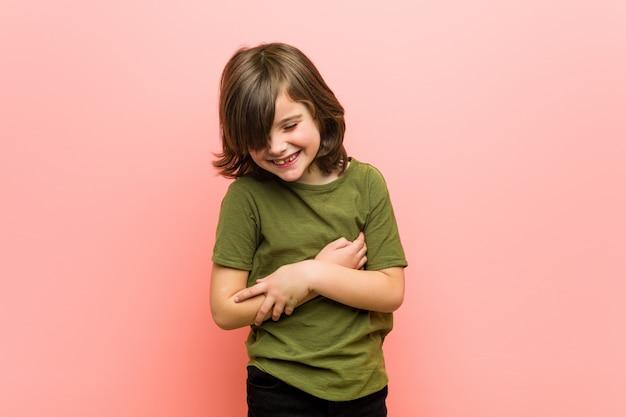 Kleine jongen lacht vrolijk en heeft plezier bij het houden van de handen op de buik.