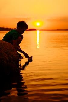 Kleine jongen lancering papier schip op het water. mooie zomerse zonsondergang. papieren boot. origami.