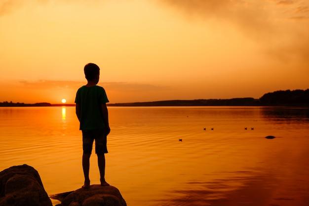 Kleine jongen lancering papieren schepen vanaf de rivier. drijvende schepen in de verte. mooie zonsondergang. origami. rivier. meer.