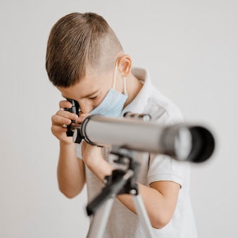 Kleine jongen leert hoe hij een telescoop moet gebruiken