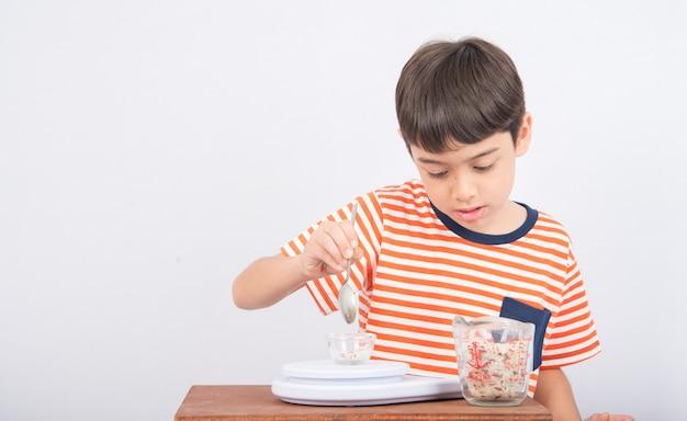 Kleine jongen leunend gewicht schaal onderwijs in de klas