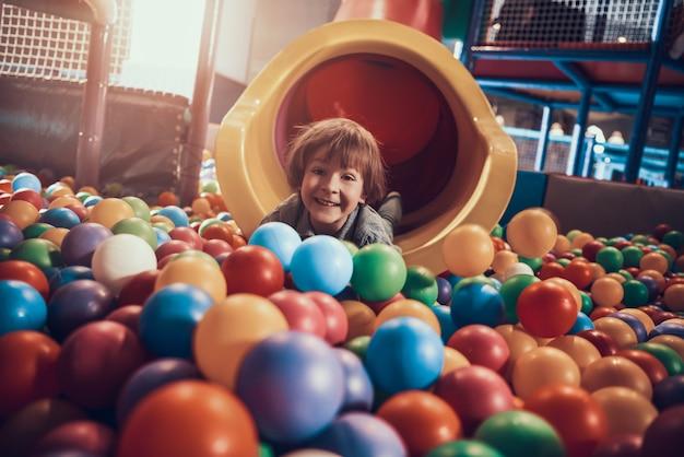 Kleine jongen liggend in zwembad vol met kleurrijke ballen
