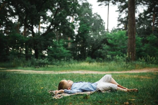 Kleine jongen liggend op de deken op het gras in het groene zomerpark