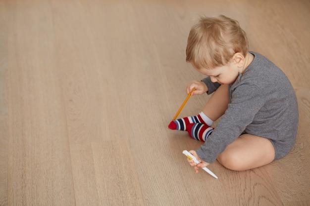 Kleine jongen liggend op de vloer in de woonkamer