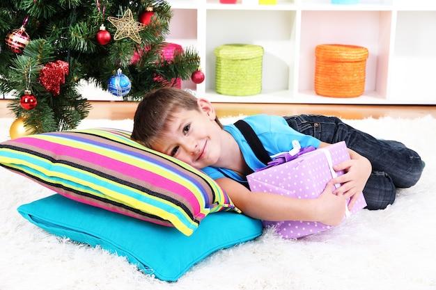 Kleine jongen liggend op kussens met cadeau in zijn handen onder de kerstboom, wachtend op de komst van de kerstman