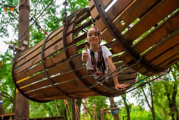 Kleine jongen loopt een hindernisbaan in een touwpark