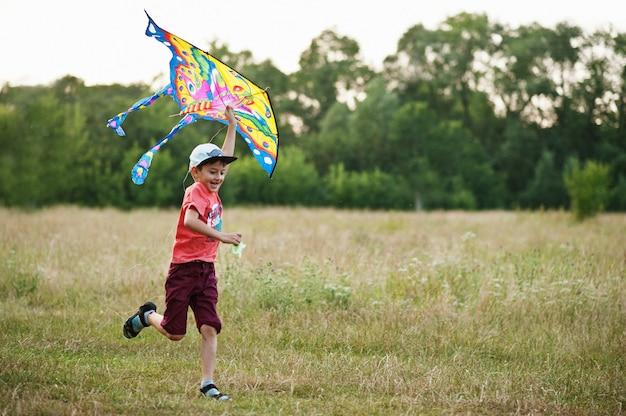 Kleine jongen loopt met vlieger in het veld in het park.