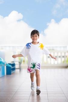 Kleine jongen loopt op school met een blij gezicht