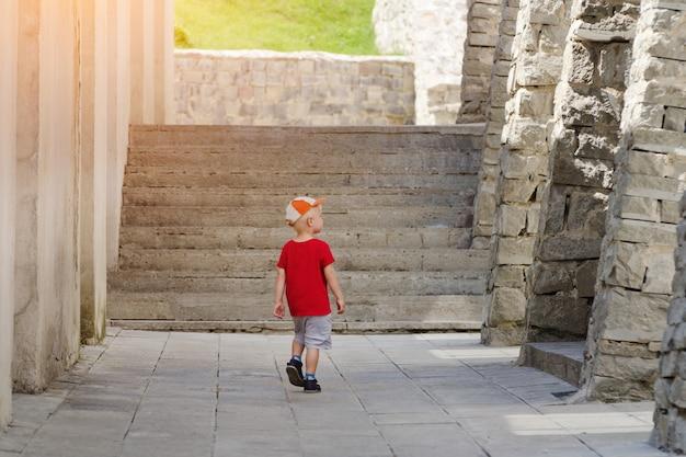 Kleine jongen lopen alleen tussen de oude muren, zonlicht.