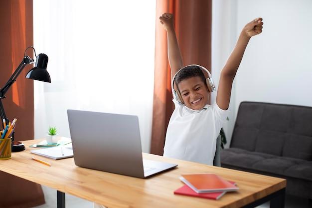 Kleine jongen luistert naar zijn leraar via een koptelefoon