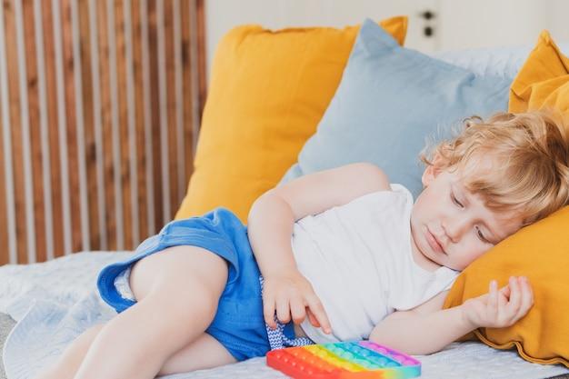 Kleine jongen met anti-stress zintuiglijk pop-it-speelgoed in zijn hand jonge peuter speelt met zintuiglijk speeltje