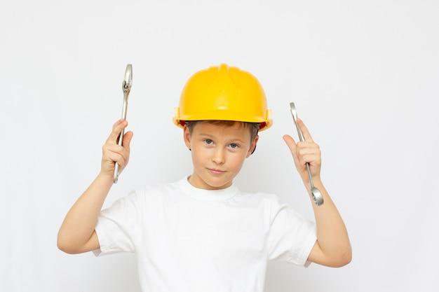 Kleine jongen met behulp van gereedschap thuis kleine bouwer in de helm en zag het werk van het nadenken over de toekomst