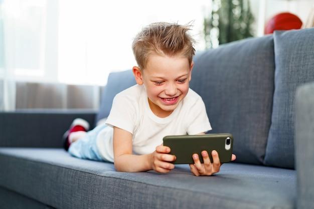 Kleine jongen met behulp van smartphone liggend op de bank thuis, portret