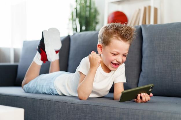 Kleine jongen met behulp van smartphone liggend op de bank thuis