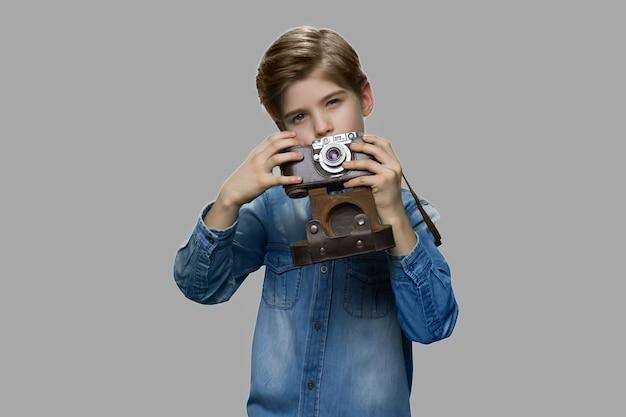 Kleine jongen met behulp van vintage camera. preteenjongen in spijkerjasje dat foto met oude retro camera neemt.