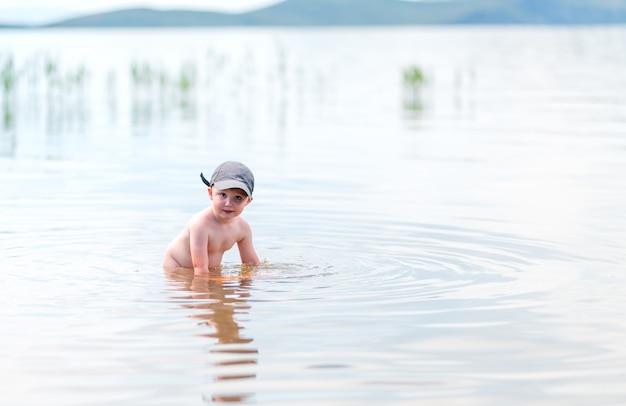 Kleine jongen met blond haar heeft plezier in zee zwemmen, zomer, verharding