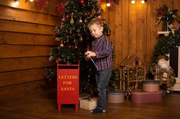Kleine jongen met brief aan de kerstman in de brievenbus van kerstmis.