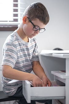 Kleine jongen met bril zit aan zijn bureau voor een laptop op zoek naar iets in een la.