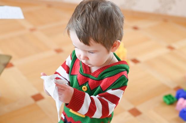 Kleine jongen met donker haar die een tissue gebruikt om zijn neus te reinigen van verkoudheid of pollenallergieën.