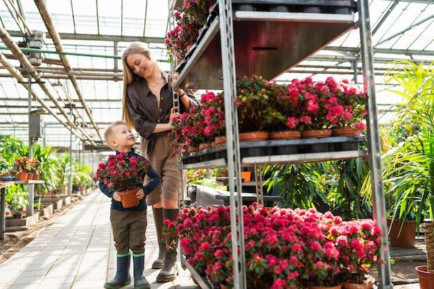 Kleine jongen met een bloem in een pot en zijn moeder