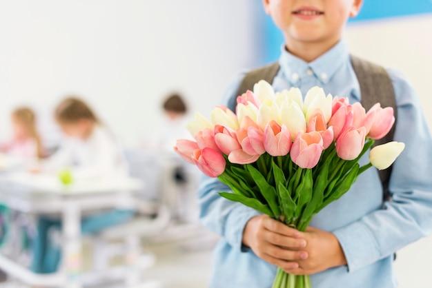 Kleine jongen met een boeket bloemen voor zijn leraar