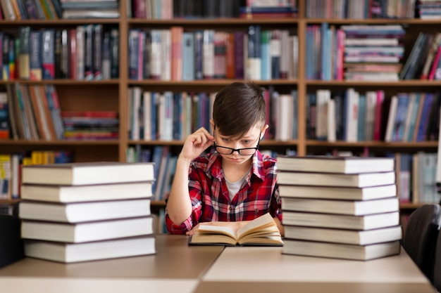 Kleine jongen met een bril bij de bibliotheek