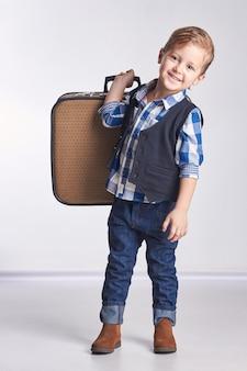 Kleine jongen met een koffer die op vakantie gaat en reist