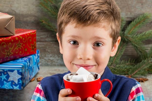 Kleine jongen met een kop warme chocolademelk met marshmallows op de achtergrond van geschenken, kerstboom en kerstversiering