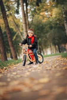 Kleine jongen met een loopfiets in de stad in de herfst
