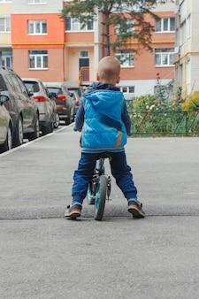 Kleine jongen met een loopfiets langs het pad in de binnenplaats op een zonnige zomerdag