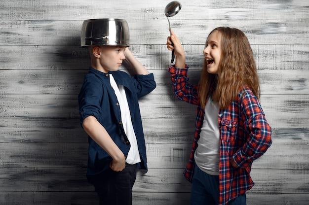 Kleine jongen met een pot op zijn hoofd en meisje met de pollepel in hand in de studio. kinderen spelen, kinderen geïsoleerd op houten achtergrond, kind fotosessie
