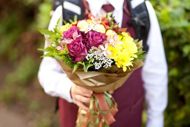 Kleine jongen met een rugzak met bloemen gaat naar school. achteraanzicht. terug naar schoolfeest.