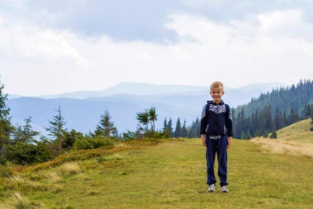 Kleine jongen met een rugzak wandelen in de schilderachtige zomer groene karpaten. kind dat alleen genietend van de mening van de landschapsberg. actief levensstijl, avontuur en weekend activiteitsconcept.
