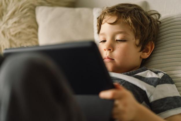 Kleine jongen met een tablet in de kamer