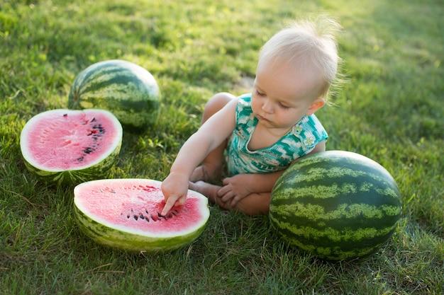 Kleine jongen met een watermeloen zittend op het gras