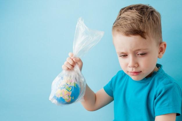 Kleine jongen met een wereldbol in een pakket op een blauwe achtergrond