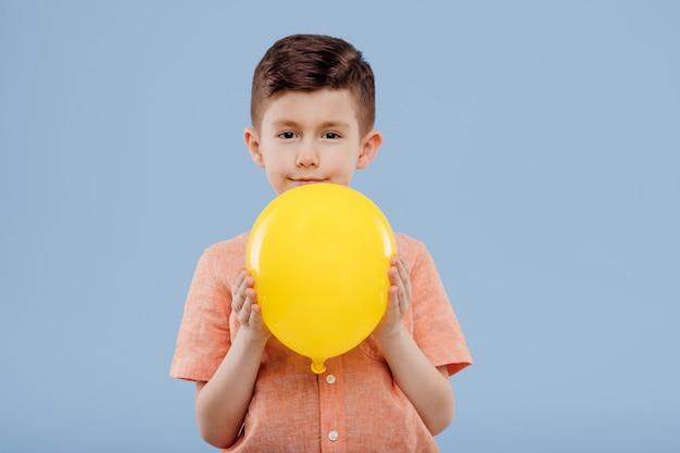 Kleine jongen met gele ballon. kijkt naar de camera, geïsoleerd op een blauwe achtergrond, kopieer ruimte