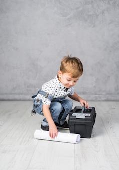 Kleine jongen met gereedschapskist en papierrol