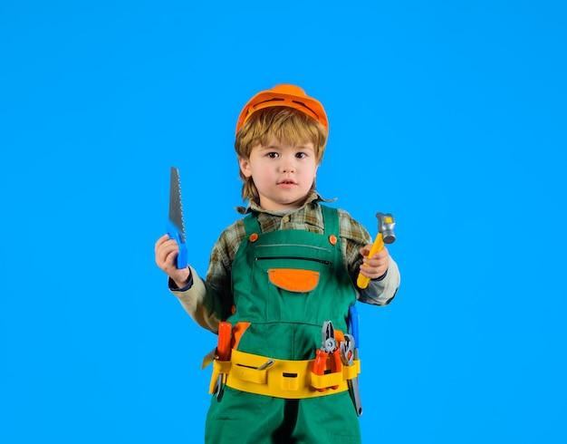 Kleine jongen met helm en gereedschap kleine reparateur als bouwvakker kleine jongen in bouwers