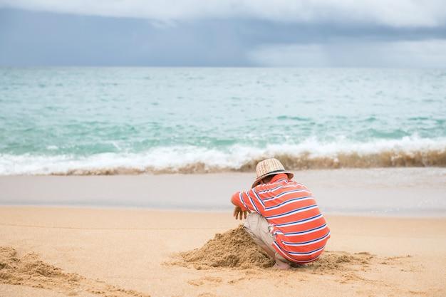 Kleine jongen met hoed maken zandkasteel op strand