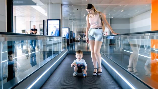 Kleine jongen met jonge moeder die op de horizontale roltrap staat in de luchthaventerminal.